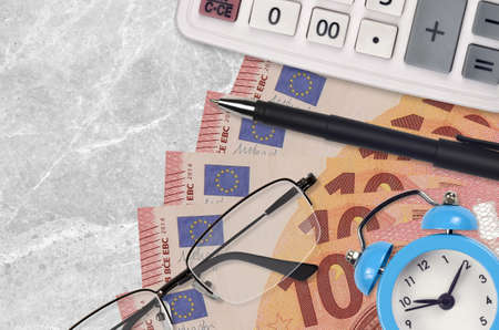 10 euro bills and calculator with glasses and pen. Business loan or tax payment season concept. Financial planning and time to pay taxes Banco de Imagens