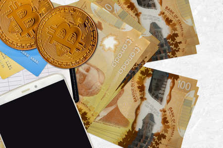 100 Canadian dollars bills and golden bitcoins with smartphone and credit cards. Cryptocurrency investment concept. Crypto mining or trading transactions