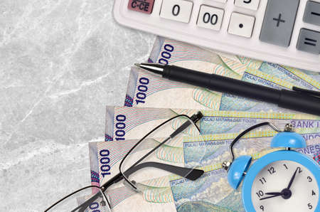 1000 Indonesian rupiah bills and calculator with glasses and pen. Business loan or tax payment season concept. Financial planning and time to pay taxes