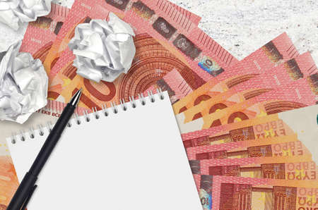 10 euro bills and balls of crumpled paper with notepad. Bad ideas or less of inspiration concept. Searching ideas for investment