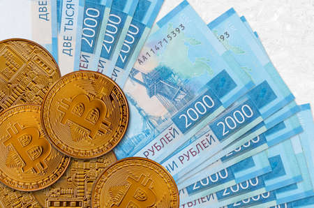 2000 russian rubles bills and golden bitcoins. Cryptocurrency investment concept. Crypto mining or trading transactions Banco de Imagens