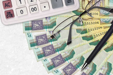1000 Sri Lankan rupees bills fan and calculator with glasses and pen. Business loan or tax payment season concept. Financial planning