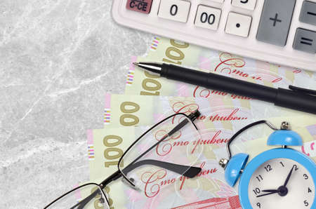 100 Ukrainian hryvnias bills and calculator with glasses and pen. Business loan or tax payment season concept. Financial planning and time to pay taxes Banco de Imagens