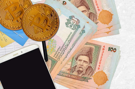 100 Ukrainian hryvnias bills and golden bitcoins with smartphone and credit cards. Cryptocurrency investment concept. Crypto mining or trading transactions Imagens