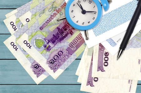 100 Cambodian riels bills and alarm clock with pen and envelopes. Tax season concept, payment deadline for credit or loan. Financial operations using postal service. Quick money transfer Banco de Imagens