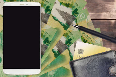 20 Canadian dollars bills and smartphone with purse and credit card. E-payments or e-commerce concept. Online shopping and business with portable devices usage