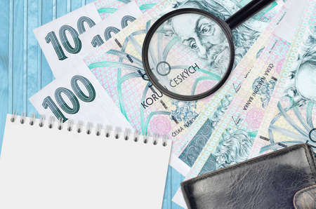 100 Czech korun bills and magnifying glass with black purse and notepad. Concept of counterfeit money. Search for differences in details on money bills to detect fake money