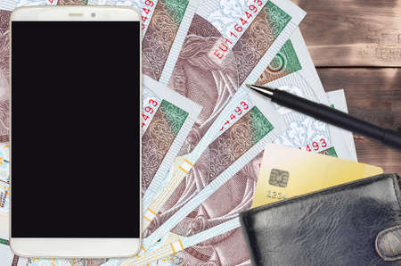 10 Polish zloty bills and smartphone with purse and credit card. E-payments or e-commerce concept. Online shopping and business with portable devices usage