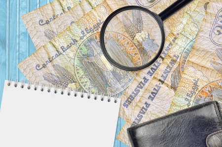 25 Egyptian piastres bills and magnifying glass with black purse and notepad. Concept of counterfeit money. Search for differences in details on money bills to detect fake money