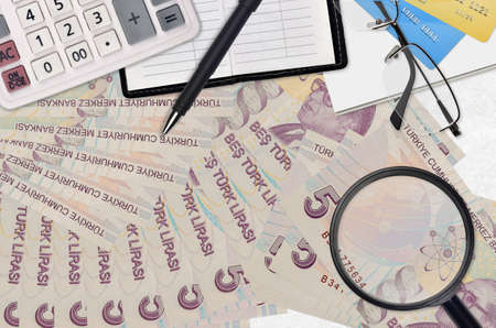 5 Turkish lira bills and calculator with glasses and pen. Tax payment season concept or investment solutions. Searching a job with high salary earnings
