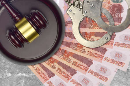 5000 russian rubles bills and judge hammer with police handcuffs on court desk. Concept of judicial trial or bribery. Tax avoidance or tax evasion