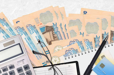 200 Ukrainian hryvnias bills and calculator with glasses and pen. Tax payment season concept or investment solutions. Financial planning or accountant paperwork Banco de Imagens