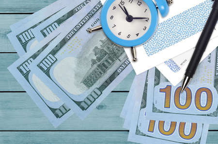 100 US dollars bills and alarm clock with pen and envelopes. Tax season concept, payment deadline for credit or loan. Financial operations using postal service. Quick money transfer