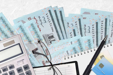 5 Egyptian pounds bills and calculator with glasses and pen. Tax payment season concept or investment solutions. Financial planning or accountant paperwork