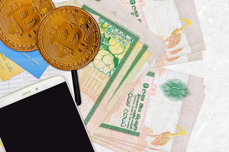 10 Sri Lankan rupees bills and golden bitcoins with smartphone and credit cards. Cryptocurrency investment concept. Crypto mining or trading transactions Banco de Imagens