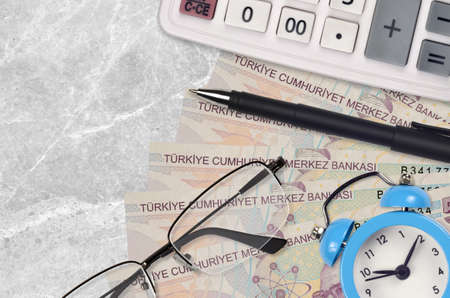 5 Turkish lira bills and calculator with glasses and pen. Business loan or tax payment season concept. Financial planning and time to pay taxes