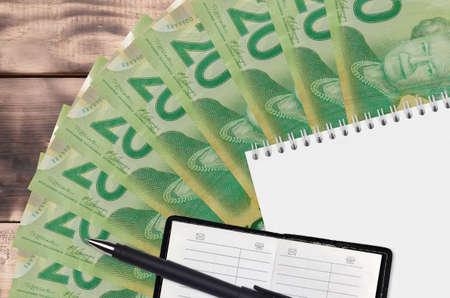 20 Canadian dollars bills fan and notepad with contact book and black pen. Concept of financial planning and business strategy. Accounting and investment