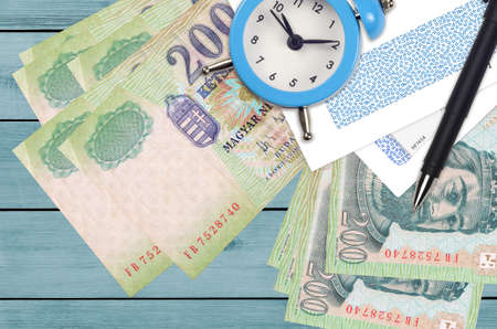 200 Hungarian forint bills and alarm clock with pen and envelopes. Tax season concept, payment deadline for credit or loan. Financial operations using postal service. Quick money transfer Banco de Imagens