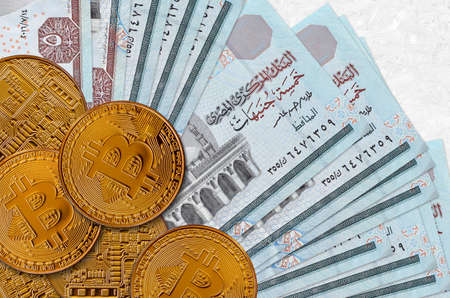 5 Egyptian pounds bills and golden bitcoins. Cryptocurrency investment concept. Crypto mining or trading transactions Banco de Imagens