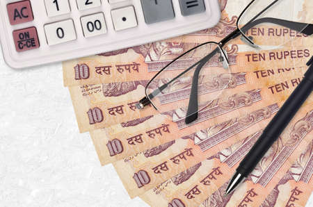 10 Indian rupees bills fan and calculator with glasses and pen. Business loan or tax payment season concept. Financial planning
