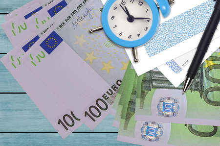 100 Euro bills and alarm clock with pen and envelopes. Tax season concept, payment deadline for credit or loan. Financial operations using postal service. Quick money transfer Banco de Imagens