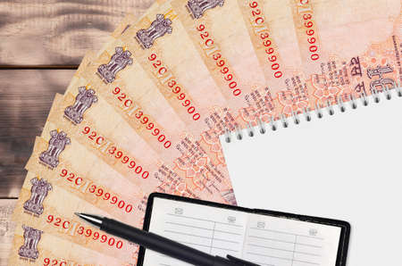 10 Indian rupees bills fan and notepad with contact book and black pen. Concept of financial planning and business strategy. Accounting and investment Stock Photo
