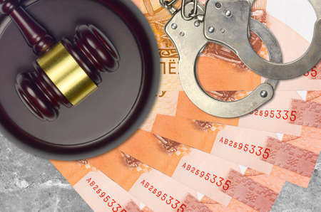 5 Belorussian rubles bills and judge hammer with police handcuffs on court desk. Concept of judicial trial or bribery. Tax avoidance or tax evasion