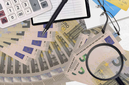 5 euro bills and calculator with glasses and pen. Tax payment season concept or investment solutions. Searching a job with high salary earnings