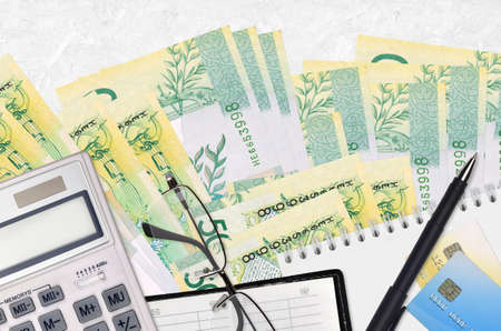 50 Belorussian rubles bills and calculator with glasses and pen. Tax payment season concept or investment solutions. Financial planning or accountant paperwork Banco de Imagens