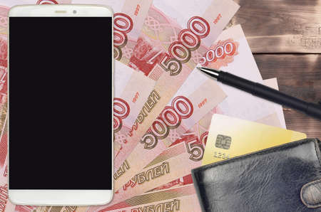 5000 russian rubles bills and smartphone with purse and credit card. E-payments or e-commerce concept. Online shopping and business with portable devices usage