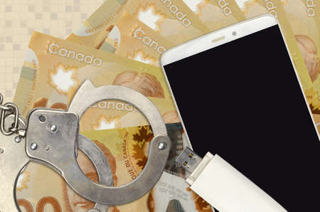 100 Canadian dollars bills and smartphone with police handcuffs. Concept of hackers phishing attacks, illegal scam or online spyware soft distribution