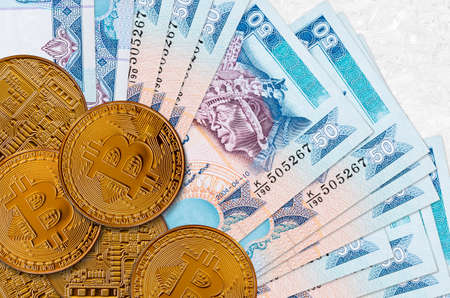 50 Sri Lankan rupees bills and golden bitcoins. Cryptocurrency investment concept. Crypto mining or trading transactions Banco de Imagens