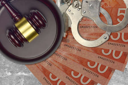 50 Canadian dollars bills and judge hammer with police handcuffs on court desk. Concept of judicial trial or bribery. Tax avoidance or tax evasion