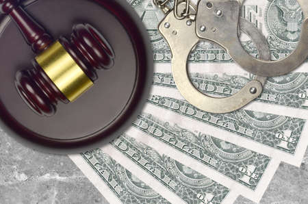 1 US dollar bills and judge hammer with police handcuffs on court desk. Concept of judicial trial or bribery. Tax avoidance or tax evasion