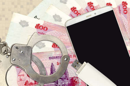 500 Cambodian riels bills and smartphone with police handcuffs. Concept of hackers phishing attacks, illegal scam or online spyware soft distribution Banco de Imagens
