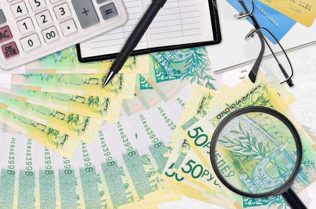 50 Belorussian rubles bills and calculator with glasses and pen. Tax payment season concept or investment solutions. Searching a job with high salary earnings