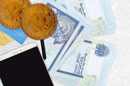 50 Sri Lankan rupees bills and golden bitcoins with smartphone and credit cards. Cryptocurrency investment concept. Crypto mining or trading transactions Banco de Imagens