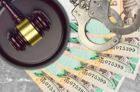 10 Sri Lankan rupees bills and judge hammer with police handcuffs on court desk. Concept of judicial trial or bribery. Tax avoidance or tax evasion 版權商用圖片