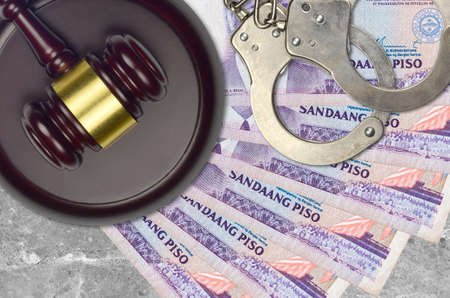 100 Philippine piso bills and judge hammer with police handcuffs on court desk. Concept of judicial trial or bribery. Tax avoidance or tax evasion