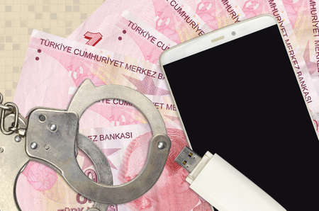 10 Turkish liras bills and smartphone with police handcuffs. Concept of hackers phishing attacks, illegal scam or online spyware soft distribution