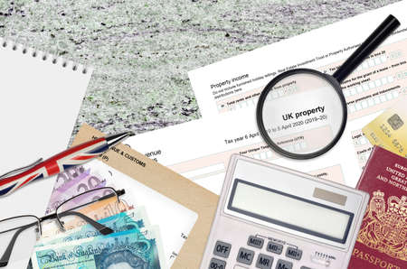 English Tax form sa105 UK Property from HM revenue and customs lies on table with office items. HMRC paperwork and tax paying process in United Kingdom of Great Britain