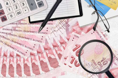 10 Turkish liras bills and calculator with glasses and pen. Tax payment season concept or investment solutions. Searching a job with high salary earnings