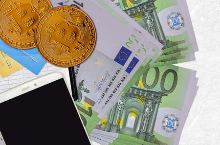 100 Euro bills and golden bitcoins with smartphone and credit cards. Cryptocurrency investment concept. Crypto mining or trading transactions