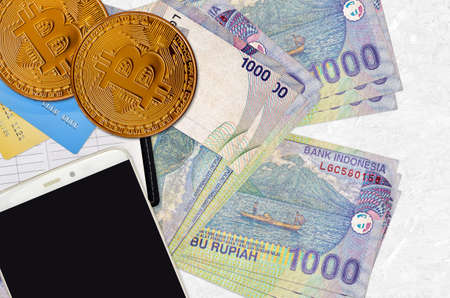 1000 Indonesian rupiah bills and golden bitcoins with smartphone and credit cards. Cryptocurrency investment concept. Crypto mining or trading transactions