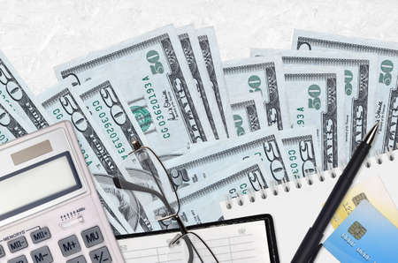 50 US dollars bills and calculator with glasses and pen. Tax payment season concept or investment solutions. Financial planning or accountant paperwork