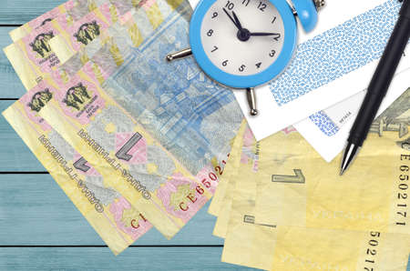 1 Ukrainian hryvnia bills and alarm clock with pen and envelopes. Tax season concept, payment deadline for credit or loan. Financial operations using postal service. Quick money transfer
