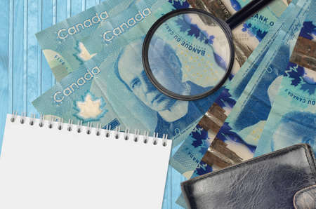 5 Canadian dollars bills and magnifying glass with black purse and notepad. Concept of counterfeit money. Search for differences in details on money bills to detect fake money