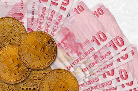 10 Turkish liras bills and golden bitcoins. Cryptocurrency investment concept. Crypto mining or trading transactions