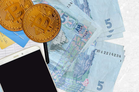 5 Ukrainian hryvnias bills and golden bitcoins with smartphone and credit cards. Cryptocurrency investment concept. Crypto mining or trading transactions