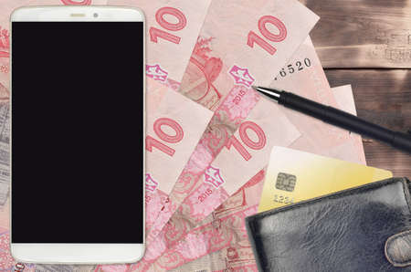 10 Ukrainian hryvnias bills and smartphone with purse and credit card. E-payments or e-commerce concept. Online shopping and business with portable devices usage